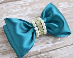 A bow clip made for your princess! This designer bow is handmade and features the most adorable grosgrain ribbon bow adorned with high quality pearls in the center of the bow. The perfect accessory for any and every event. Proudly made in the USA. Sold as an individual piece.