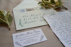 Watercolor calligraphy on light green envelope with vintage stamps