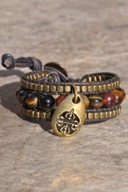 """""""Judith"""" A beaded cuff bracelet of brown leather, multi-shaded beads, brass-toned beads, and an antiqued charm. Like Judith, be a woman of steadfast trust in the Lord knowing He is watching over you and will deliver you from difficult situations with perfect timing. He works all things for the good of those who love Him because He first loved us."""