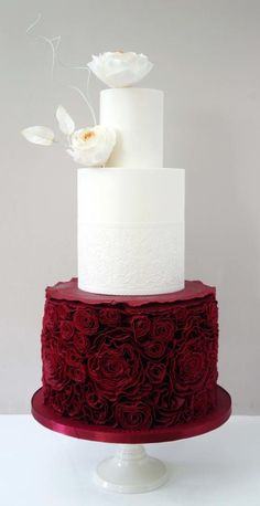 Red white and flowers Bottom Tier is a double barrel deep burgundy red with ruffles rossettes all around which took me forever :) and the 2 top tiers are white with the middle tier having an edible...