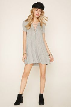 In a marled knit, this mini dress features a lace-up neckline, short sleeves, and an A-line silhouette.