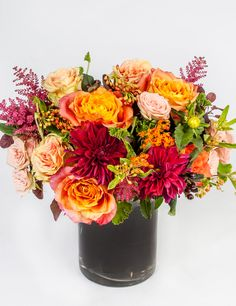 Saffron Sunset - A bold mixture of oranges, peaches, burgundies and greens - including dahlias, roses and astilbe - is gathered in cylinder vase lined with a dark burgundy ti leaf.