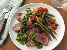 Food Network invites you to try this Grilled Steak with Green Beans, Tomatoes and Chimichurri Sauce recipe from Food Network Kitchens.