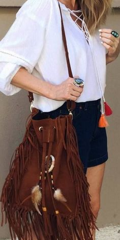 This oversized suede bucket bag comes in a rustic shade of brown and features fringe tassels on the side. The dreamcatcher in the middle adds a hippie touch to this large bucket bag that can carry eve