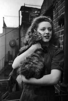 A young woman with a pet cat, 11th April 1942. Original publication: Picture Post - 1103 - A Day In The Life Of A Warship Week. Brittania - pub. 1942. (Photo by Haywood Magee/Picture Post/Hulton Archive/Getty Images)