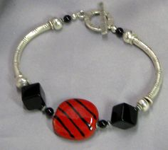 Kazuri Bangle Bracelet in Red and Black. Unique handmade Kazuri  with wrist noodle tubes make this a very interesting bangle bracelet Available at VP's Jewelry BOutiqu