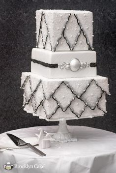 Sparkling Winter Wedding Cake by Brooklyn Cake. This wedding cake was inspired by winter, covered in sparking sugar and shiny decoratifs. This cake tries to capture an antique feel with a quilted tier and antique-style ornaments.