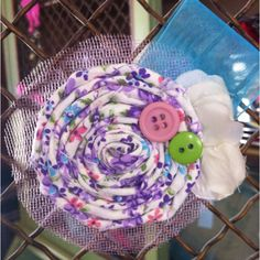 Rolled fabric flower w/tulle, buttons, & ribbon accents. This is a clip that can be used alone or attached to a headband.