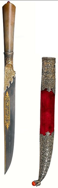 Ottoman kard (straight dagger), jade hilt, with a ruby set in gold, watered-steel blade, the forte with gold-inlaid inscriptions in a lobed cartouche,  niello mount depict a figure,  (a sultan?), standing outside a palace with a bird of prey,  velvet scabbard, the locket and chape with niello scenes of the sultan, chased and engraved in high relief with an arabesque of tendrils, leaves and hatayi flowers on the reverse, terminating with dragon headed finial clasping a coral bead.