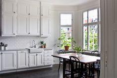 Vitt kök, gråa beslag, grå bänkskiva och mörkt golv. Snyggt!!