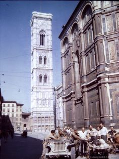 American and British soldiers stop to talk to an invalid woman on push cart. Famous Tower of Campanile De Giotto can be seen in background.