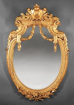 "*LOUIS XVI-STYLE CARVED and GILT MIRROR ~ late 19th c., crest centered by cartouche with entwined monogram ""HM"", flanked by female terms, beveled mirror plate, shield-shape with acanthine and beaded border, height 55 in., width 38 in., depth 7 1/2 in. Provenance: ""Villa Rose"" Collection of Grace Collins Lindblom, Orlando, FL"