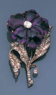 A late 19th century amethyst and diamond pansy brooch, circa 1880 The single bloom with carved amethyst petals and central cushion-shaped diamond, weighing 1.53 carats, to realistically modelled leaves and stem set throughout with old brilliant-cut diamonds, hinged bangle fitting supplied, inner diameter 5.4cm., one diamond deficient, remaining diamonds approximately 3.90 carats total, brooch height 7.6cm.