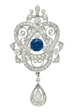 A Sapphire and Diamond Pendant Necklace, Birks.  Centering a round sapphire weighing approximately 2.30 carats, amid a stylised diamond-set trefoil Endless knot and scroll decorations, and suspending a pear-shaped diamond drop, suspending from a fine box linking necklet, length 15 ins, mounted in 18k white gold, signed Birks, with original box