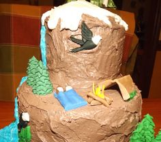 Close up of mountain camping cake - for once, no need to smooth the buttercream - you want it rough for the mountain appearance. Waterfall is blue and white buttercream mixed in bag for white water effect. Campfire, campers, tent and bald eagle from fondant.