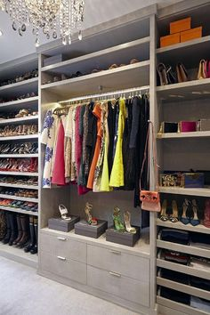 Monique Lhuillier - Gray walk-in closet features a wall of floor to ceiling gray built-ins boasting stacked gray shelves stacked over a lighted clothes rail and built in drawers flanked by gray shelves filled with designer shoes and handbags illuminated by a crystal drops chandelier.