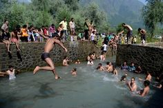 July 14, 2013. A Kashmiri Muslim boy jumps in a spring during a hot Ramadan day in the outskirts of Srinagar as Kashmir Valley undergoes a heat wave during the holy month. Syed Shahriyar—Demotix/Corbis