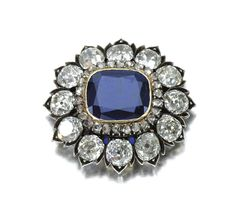 An 1880s brooch with a cushion-shaped sapphire set within a frame of rose diamonds and a further border of circular-cut stones in foliate mounts