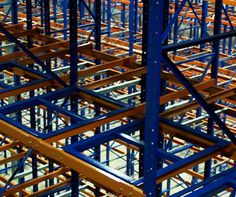 """Push Back rack high density storage rack designed to allow for both selectivity and dense storage. Push Back rack is named such because the pallet is placed by the lift truck onto a """"cart"""" and then """"pushed back"""" into the rack by the next pallet being loaded into the rack system"""