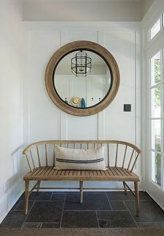 Simple entry. The curves of the bench and the round mirror draws your eye away from the small square space of this entry.