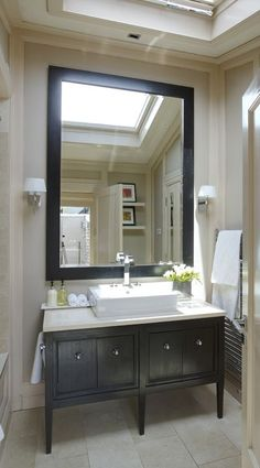 I love the oversize mirror in this bathroom and the furniture-style vanity. By designer Gail Wall Morris, who renovated her tiny former workman's cottage in Dublin, Ireland.