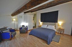 """Villa Velleron's elegant """"Luberon"""" room: on the 2nd floor of the main building. Romantic view over the village's roofs. Double bed 160x200cm, 2 armchairs, small table, wardrobe, air condition, refrigerator. Integrated bathroom with spacious shower, basin and hairdryer, separate toilet."""