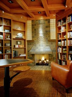 This regal library displays a collection of books and features open shelving to showcase sports memorabilia. The stone fireplace acts as the focal point, providing a comfortable spot to stay warm while reading.