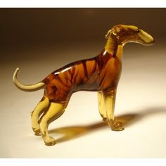 """This brown glass greyhound is poised like a rubber band, ready to snap into high gear. At maximum speed, they can reach up to 70 kilometers per hour, making them one of the fastest animals in the world. For all their speed however, greyhounds make sweet, gentle pets that love to snuggle with their chosen human. This beautiful depiction of the greyhound will make it a wonderful addition to your dog collection. Size: L - 2.0"""" H - 1.5"""" W - 1.0"""""""