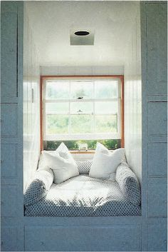 Love the cushy window seat tucked into a dormer surrounded by built-ins!