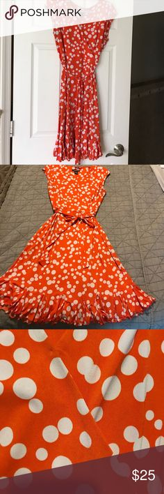 Polka dot dress Chic orange and white polka dot dress. Worn in excellent condition. Wrap style top and flare alone bottom. Fabric is stretchy so you will put on over your head. No zippers. Cap sleeves and a self tie belt. The wrap top may open on a fuller breast so I wore with a pin. You may see pic for the pin trace is. Size 12 and although lift fabric no need for lining. Hits at knee Dresses
