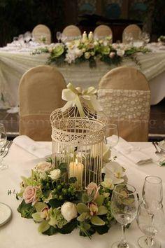 Δεξιωση γαμου στολισμός στο τραπέζι σας με λουλούδια και ένα κλουβί.