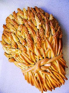 "Wheat sheaf bread. make long ""snakes"" of dough, and snip feathery patterns into the end with kitchen shears. Wrap an extra-long snake around them and bake."