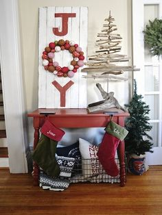 "A wreath serves as the ""O"" in an a ""Joy"" sign that Liz painted on weathered wooden planks. The driftwood tree packs an architectural and organic punch, offering a creative alternative to tabletop firs."