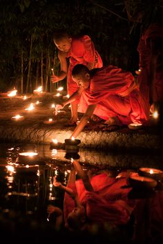 Young monks lighting up candles during Visakha Bucha in Chiang Mai, Thailand.  √