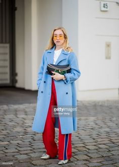 BERLIN, GERMANY - APRIL 04: Sonia Lyson wearing glitter booties Jimmy Choo, red track suit pants Zara, baby blue cashmere coat Zara, Miu Miu fanny belt bag, Topshop sunglasses, white tshirt, Bucherer watch is seen on April 4, 2018 in Berlin, Germany. (Photo by Christian Vierig/Getty Images)