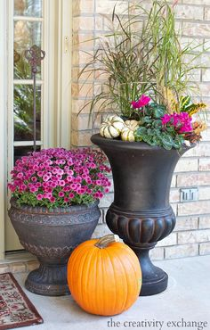 Mix tall grasses, fall plants and small pumpkins together in large urns for fall.  More fall porch decorating ideas from The Creativity Exchange