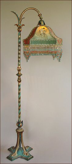 "Exceptional Moe Bridges 1920 era bridge lamp with original paint in aqua and red. Custom Gent shade dyed gold to aqua and covered in antique metallic gold lace and 19th century appliqués. Incredibly rich, red and gold silk with gothic motifs finish the corner panels. Hand beaded fringe in matching tones finish the lampshade. Height 57""."