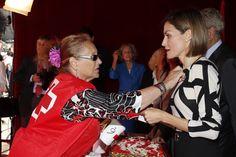Una voluntaria de Cruz Roja le impone la insignia a Su Majestad la Reina Letizia tras realizar una donación. Congreso de los Diputados. Madrid, 02.10.2015