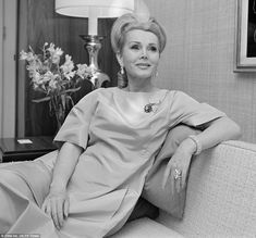 Zsa Zsa Gabor cuts an elegant figure as she relaxes on a sofa wearing a cocktail dress and adorned in diamond earrings, a ring and brooch
