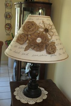 I painted and distressed base of the lamp black.  Shade is off white and I used a black fabric pen to paint the words to a song, Sing Cheerfully, Sing Joyfully around the shade.  I made the flowers from burlap and twine with vintage buttons in the center of 2 of the flowers.  I glued twine around the bottom and top of the edge of the shade.