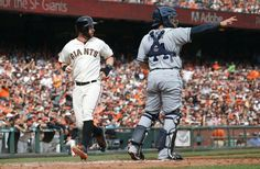 San Francisco Giants' Brandon Belt, left, scores a run past San Diego Padres catcher Rene Rivera during the second inning of a baseball game in San Francisco, Sunday, Sept. 28, 2014. (AP Photo/Tony Avelar)