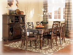 """The warm rustic beauty of the """"Porter"""" dining room collection uses a deep finish and ornate details to create an inviting furniture collection that fits comfortably into the decor of any dining area. The rich look of the burnished brown finish flows beautifully over the decorative framed details. With the dark bronze color hardware and beautifully styled scoop saddle seat chairs, the """"Porter"""" dining room collection is the perfect choice for any home environment. Made by Ashley Furniture"""