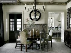 Alternating painted and upholstered dining chairs offer a chic counterpoint to reclaimed barn beams overhead in the great room. The designer added a sturdy Black Forest wood china cabinet for an overt mountain reference.