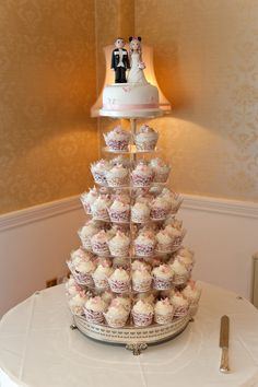 Our cupcake wedding cake with fruit-cake top tier - butterfly and flower decorations. Created by Sugar Sensations, Hook UK