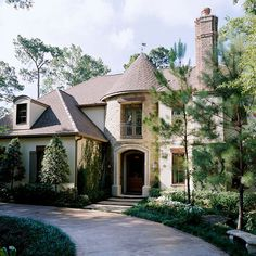 A hipped roof, a stone-covered turret, iron balconies, and a tall brick chimney set the tone for this country French-style home. The exterior boasts a specially textured and mottled cast stone that mimics the look of sienna limestone./