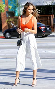 Ample assets: The 29-year-old beauty flaunted her long, lean curves in a VERY low slung orange crop top and pinstripe white culottes