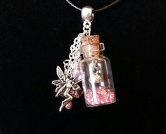 Pretty handcrafted pink bottle charm necklace filled with glitter fairy dust and contains a tiny flower charm. Also has a cute fairy charm and drop crystal and glass pearl beads. Immitation Leather 16 inch necklace.