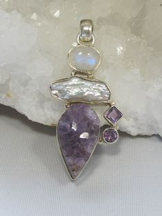 Gorgeous handmade artisan Amethyst Quartz specimen pendant accented with Rainbow Moonstone, Biwa Pearl, and 2 faceted Amethyst gemstones, set in 925-hallmarked sterling silver. Largest vertical dimens