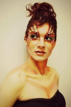 Creative gold and burgundy crystal accented fantasy makeup.