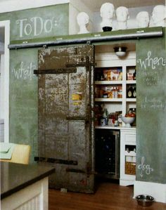 kitchen Pantry hide by old industrial door and love the chalk walls
